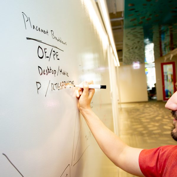 Image of a man writing on a whiteboard with a marker.