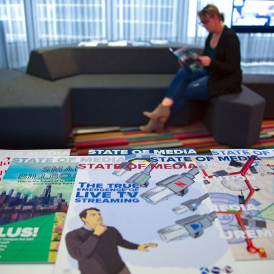 Image of a woman sitting on a couch and reading a magazine with a stack of magazines in front of her.