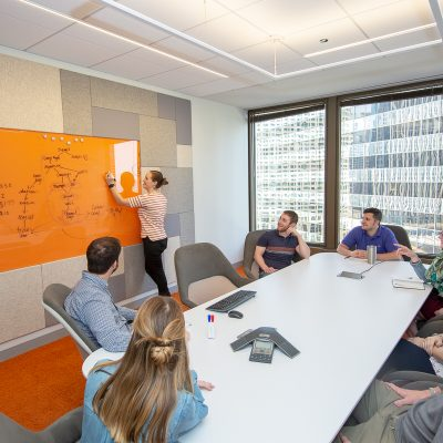 Image of a group of people sitting around a table watching a woman write on a dry erase board.